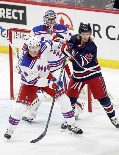 Winnipeg Jets' Kyle Connor and New York Rangers' Jacob Trouba fight for position in front of Rangers goaltender Igor Shesterkin during the first period.