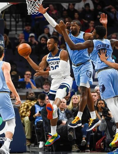 Minnesota Timberwolves guard Josh Okogie, left, passes the ball under the basket while being pursued by Memphis Grizzlies forward Solomon Hill, center, and forward Jaren Jackson Jr., right, during the first half of a NBA basketball game Sunday, Dec. 1, 2019, in Minneapolis. (AP Photo/Craig Lassig)
