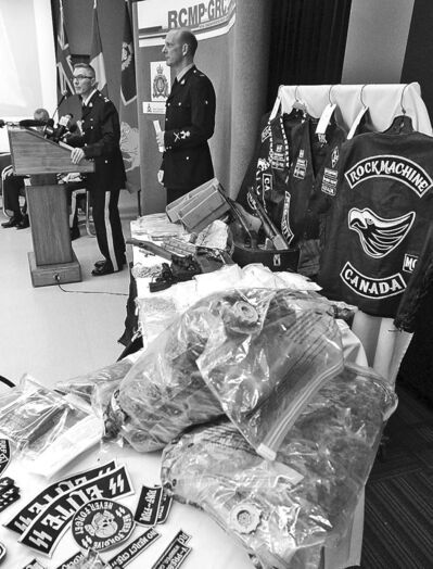 KEN GIGLIOTTI / WINNIPEG FREE PRESS RCMP officers display a haul of guns, drugs and gear seized from biker gang.