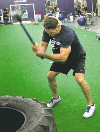 Defenceman Mark Stuart slams a tractor tire with a sledgehammer during a workout at Focus Fitness in the MTS Iceplex.