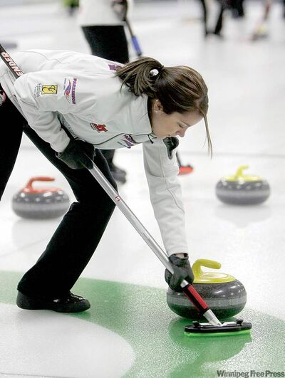 Skip Kerri Einarson pitches in with the sweeping during Sunday night's final.