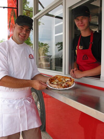 Steffen Zinn (left), of Starbuck, owns the Red Ember food truck, serving up freshly baked, handmade pizza with the help of employee Max Steinwachs.