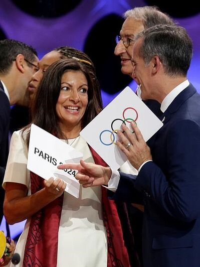 Paris Mayor Anne Hidalgo, left, speaks with Los Angeles Mayor Eric Garrett at the end of an IOC session in Lima, Peru, Wednesday, Sept. 13, 2017. The IOC is voting to ratify Los Angeles as the host city of the 2028 Olympic and Paralympic Games and Paris as the host city of the 2024 Games. (AP Photo/Martin Mejia)
