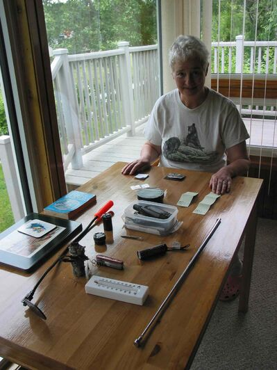 Evelyn Burch, of Headingley, shows some of the containers used to create caches and the tools used to find them.