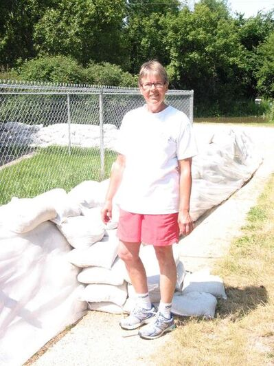 RM of Cartier public information officer Carmen Asu stands next to the sandbag dike surrounding her home on Ferry Road.