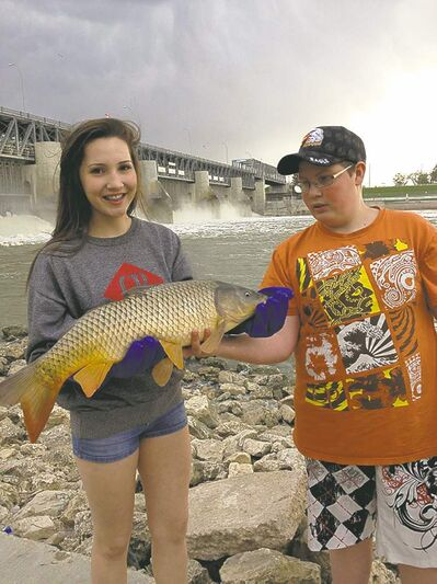Students from the Miles Mac Angling Club show off a carp they caught on the Red River at Lockport. The club raised $1,800 to help young oncology patients and their families.