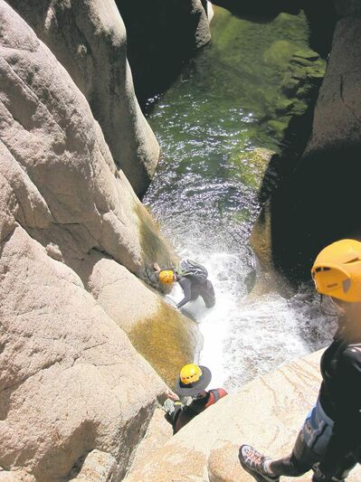 Hikers in wetsuits and helmets wading in Salome Creek in Salome Canyon, in Arizona;s Tonto National Forest. The sport of canyoneering includes hiking, climbing, sliding and wetsuit-wading but can be tackled by novices accompanied by an experienced guide.