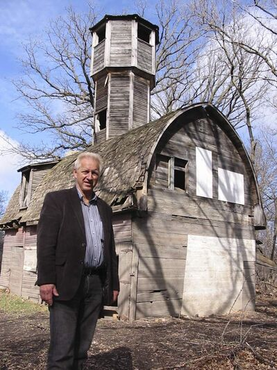 Emerson Mayor Wayne Arseny is seen outside a historic fox-fur barn and (below)  peering out its peeping tower.