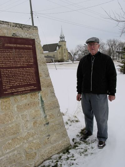 St. Francois Xavier Historical Society member Rudy Friesen stands next to a momument honouring the community's founder, Cuthbert Grant. The St. Francois Xavier Roman Catholic Church is visible across Highway 26.
