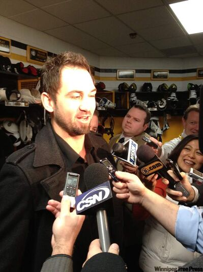 Jets radio broadcaster and former member of the Boston Bruins Shane Hnidy is swarmed by reporters in Boston's TD Garden Saturday morning.