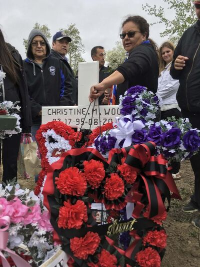 MELISSA MARTIN / WINNIPEG FREE PRESS</p><p>Melinda Wood reaches down to put one last flower stand on her daughter&#39;s grave.</p>