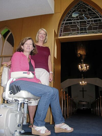 (From left) Avonlea United Church members Connie Arran and Linda Manson show off one of the two new chair lifts recently installed to improve accessibility to the church and its basement.