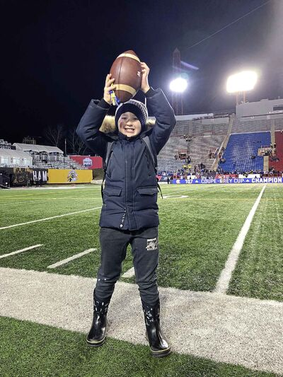 Eight-year-old Easton May with the ball that Andrew  Harris carried for his first touchdown. (Ben Waldman / Winnipeg Free Press)