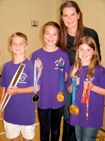 Jennifer Botterill spent time speaking with Oakenwald Elementary School's Leadership group. (From left) Aaron Kaltenthaler, Robin Maslyk and Dylan Mask were excited to hold some of Botterill's medals.
