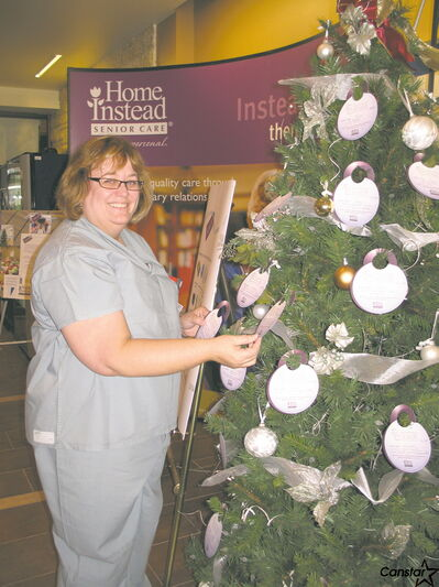 Tara Angell, a nurse at Victoria General Hospital, picks a name off the tree.