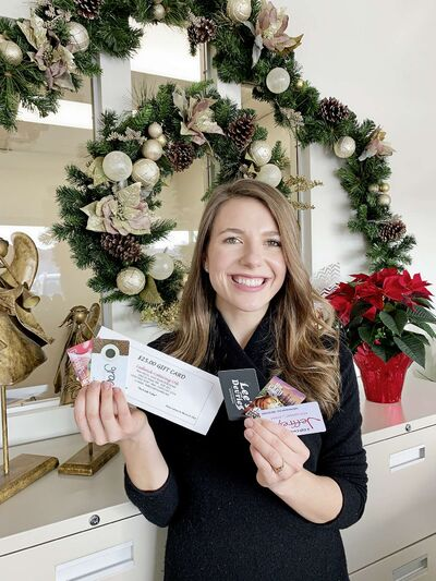 Kildonan-St. Paul MP Raquel Dancho holds gift cards purchased from local small businesses that she contributed to the Community HUB Christmas Countdown Gift Card Giveaways.