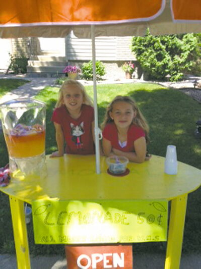 Emily Enns (standing) and Taylor Allen, both eight years old, ran a lemonade stand outside Emily's River Park South home two weekends ago, hoping to raise money for the Winnipeg Humane Society. The enterprising pair earned $112.66.