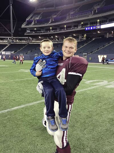 The Kildonan East Reivers's Jessie Posthumus holds up seven-year-old Isaac Scott as the Reivers celebrated their first WHSFL Bowl championship on Nov. 9 at Investors Group Field.