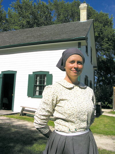 In this 2012 file photo, Monique Olivier, then director at Riel House, stands outside the historic building in period dress.