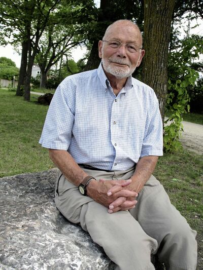 Jude Henteleff sits in front of tress planted by his forefathers.