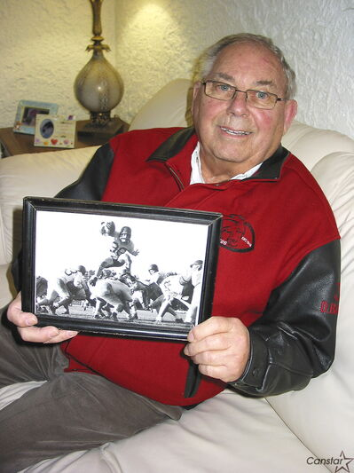 Gord Poersch holding a photo of his football playing days (he's in the air), which appeared in the Winnipeg Free Press.