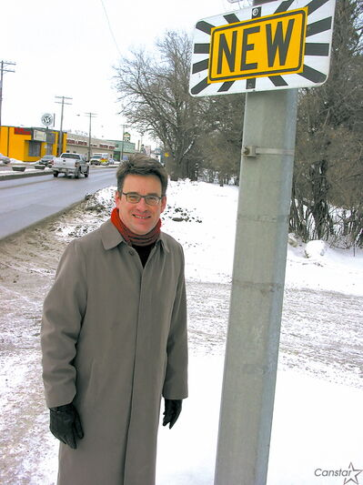 Coun. Brian Mayes (St. Vital) stands next to a new parking ban sign on St. Mary's Road near Carriere Avenue, which divides the St. Vital and St. Boniface wards.