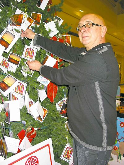 In this 2012 file photo, long-time volunteer Jim Krokosh is pictured attaching a card to the Hospice Memory Tree at St. Vital Centre.