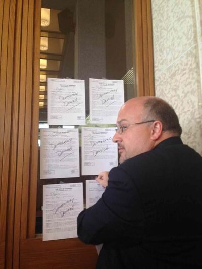 """Coun. Wyatt taping up all the amendments to the strategy that council refused to hear. Written on each paper is """"democracy denied."""""""