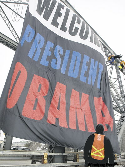 Activists secure banner on a bridge crossing Ottawa River as they prepare for visit by Obama.