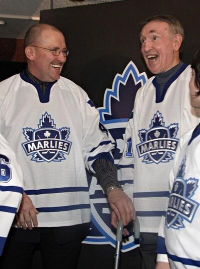 Toronto Marlies alumni Mike Pelyk (left) and Bob Nevin laugh after the new name and logo for the Toronto Maple Leafs AHL affiliate was unveiled in Toronto on Tuesday, March 22, 2005. Nevin, a fan favourite who won two Stanley Cups with the Toronto Maple Leafs before a successful run as captain of the New York Rangers, has died. He was 82.THE CANADIAN PRESS/Frank Gunn