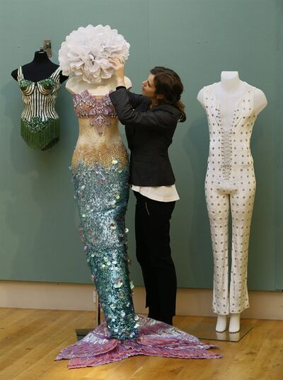 A Christie's employee adjusts a mermaid outfit decorated with Swarovski crystals worn by Katy Perry, as also in picture are stage outfits worn by Madonna, left, and Mick Jagger, right, during a photocall at the auction rooms in London, Friday, Nov. 23, 2012. The outfit estimated at 2,000- 3,000 pounds ($3,200- 4,800) will go on sale in the Pop Culture auction on Nov. 29 in London. (AP Photo/Kirsty Wigglesworth)