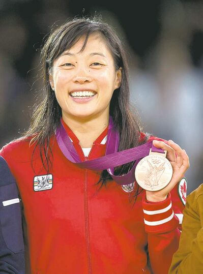 Frank Gunn / THE CANADIAN PRESSTeam Canada�s Carol Huynh shows her pride and a bronze medal, which she won Wednesday in the 48-kilogram class of women�s freestyle wrestling.