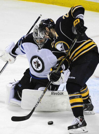 Ondrej Pavelec  makes a save on Buffalo Sabres winger Drew Stafford during a November game in Buffalo.