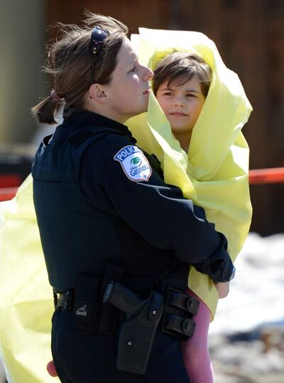 Police officer carries child from a safehouse to waiting parents and guardians in Gatineau, Que. after Friday's shooting.