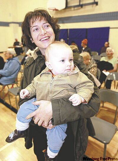 Erin Robbins and her son, Connor, eight months, wait to get their shots.