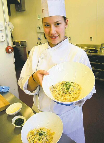 Mae Berard prepares fettuccini alfredo in the kitchen of the RRC School of Hospitality and Culinary Arts.