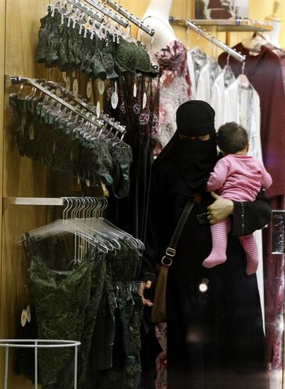 FILE - In this Wednesday, March 25, 2009 file photo, a Saudi woman holding a child checks out lingerie at a store in Riyadh, Saudi Arabia. Saudi Arabia says starting Thursday, Jan. 5, 2012, only females can work in women's lingerie stores. The 2006 law banning men from working in female apparel and cosmetic stores has never been put into effect, partly due to hard-liners in the religious establishment who oppose the whole idea of women working where men and women congregate together, like malls. (AP Photo/Hassan Ammar, File)