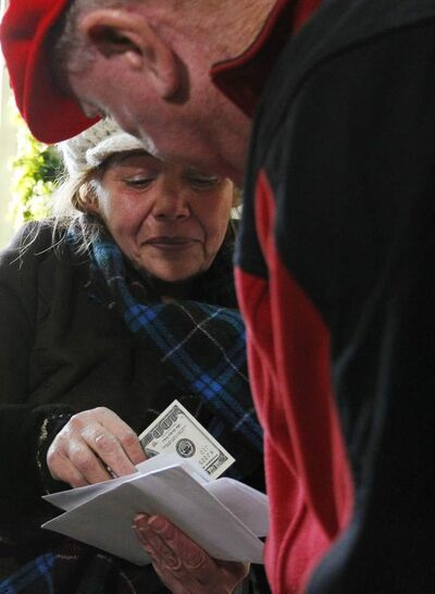 A woman receives a $100 dollar bill from a wealthy philanthropist from Kansas City, Mo., known as Secret Santa. Secret Santa distributes $100 dollar bills to needy people at St. Joseph's Social Service Center and other locations in Elizabeth, N.J., Thursday, Nov. 29.