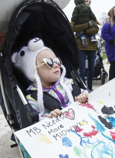 MIKE DEAL / WINNIPEG FREE PRESS FILES</p><p>Poppy Haywood, 2, holds a sign during a rally at the Manitoba Legislative building in May calling for more midwivery positions in the province.</p>