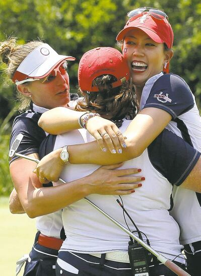 United States captain Meg Mallon (centre) whoops it up with Michelle Wie (right) and teammate Brittany Lang after the pair won their foursome match Saturday.