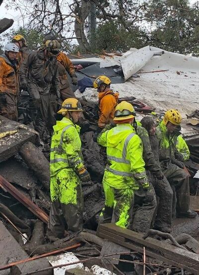 In this photo provided by Santa Barbara County Fire Department, firefighters successfully rescue a 14-year-old girl, right, after she was trapped for hours inside a destroyed home in Montecito, Calif., Tuesday, Jan. 9, 2018. Multiple people were killed and homes were swept from their foundations as mud and debris from wildfire-scarred hillsides flowed through neighborhoods and onto a key Southern California highway Tuesday during a powerful winter storm that dropped record rain across the state. (Mike Eliason/Santa Barbara County Fire Department via AP)
