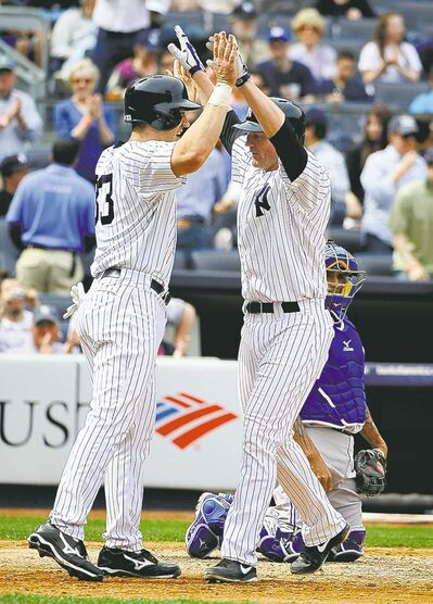 The Yankees' Travis Hafner (33) greets Lyle Overbay in front of Blue Jays catcher Henry Blanco after Overbay hit a two-run home run off of starter R.A. Dickey.