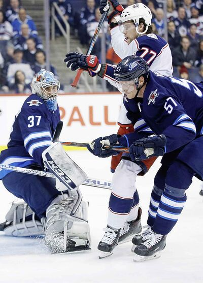 Columbus Blue Jackets' Josh Anderson scores against Winnipeg Jets goaltender Connor Hellebuyck  as Tyler Myers defends during first period NHL action, Thursday.