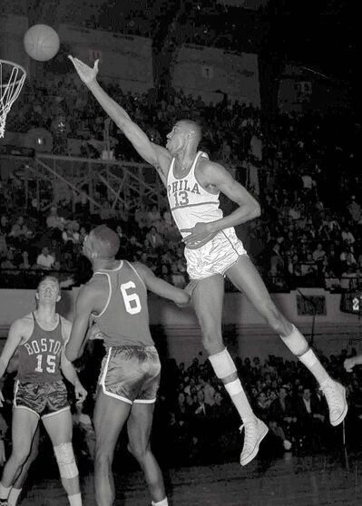 ** FILE ** Wilt Chamberlain, of the Philadelphia Warriors, shoots over Boston defenders in Philadelphia, in this March 1960 file photo. Wilt the Stilt could become Wilt the Stamp if a grassroots effort to get the Hall of Famer and the only NBA player to score 100 points in a game on a commemorative U.S postage stamp is approved by postal officials. (AP Photo/files)