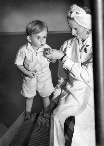 "FILE - In this June 3, 1943 file photo, physical therapist Estrid Dane carefully supports two-year-old Anthony Bull, seen here walking up a corrugated ladder during exercises which are designed to strengthen his legs in East London. Rickets, the childhood disease that once caused an epidemic of bowed legs and curved spines during the Victorian era, is making a shocking comeback in 21st-century Britain. Derived from the Old English word ""wrickken"" meaning to twist, rickets is the result of a severe deficiency of vitamin D, which helps the body absorb calcium. Rickets was historically considered to be a disease of poverty among children who toiled in factories during the Industrial Revolution and some experts have hypothesized it afflicted literary characters like Tiny Tim in Charles Dickens' ""A Christmas Carol."" (AP Photo, File)"