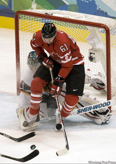 Canada's Rick Nash and German goaltender Thomas Greiss clash in a failed Can­adian scoring attempt Tuesday.