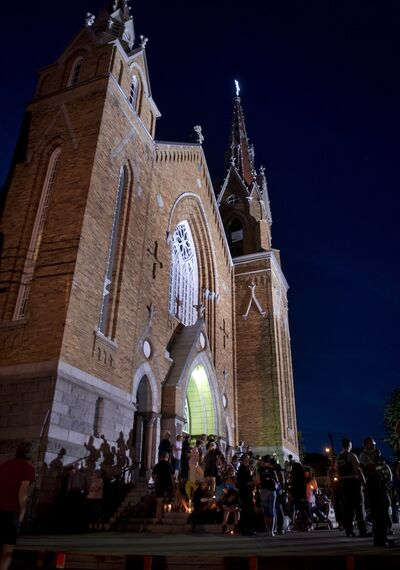 People gather in front of the St-Agnes church in Lac-Mégantic, Que. during a vigil for the victims of the July 6 train crash.