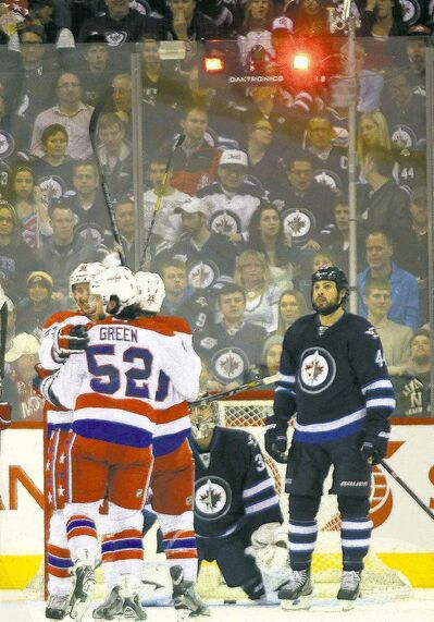 Winnipeg Jets defenceman Zach Bogosian has that here-we-go-again look as the Caps' Jay Beagle scores to make it 3-0 and chase Jets goalie Ondrej Pavelec from the net.