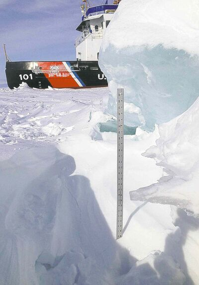 A yardstick measures the thickness of some of the ice the crew of cutter Katmai Bay, background, battles during icebreaking operations in the Straits of Mackinac.