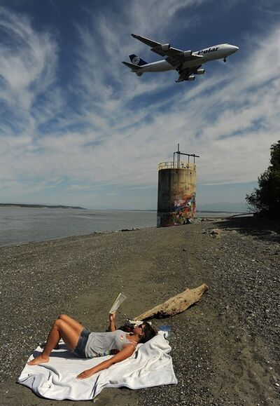 Liz Gobeski soaks up the sun on the beach at Point Woronzof as a Polar Air Cargo jet comes in for a landing at Ted Stevens Anchorage International Airport as the temperature reached into the 80's in Anchorage, AK on Tuesday, June 18, 2013. (AP Photo/Anchorage Daily News, Bob Hallinen)